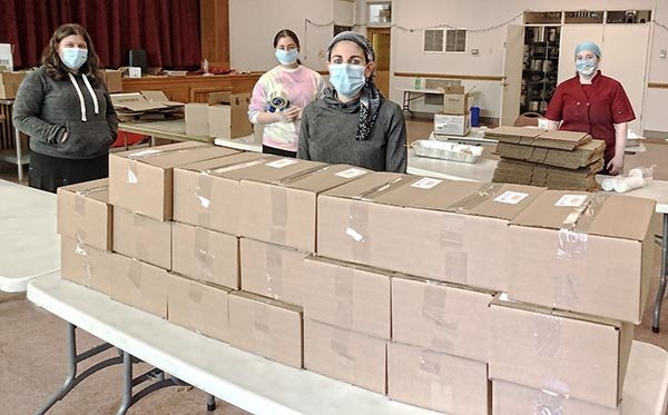 Volunteers organize boxes in the social hall at Congregation Beth Sholom during the first Kosher lunch distribution. From left, Nadia Benz, PHDS graduate, Chavi Saklad, PHDS senior, Rachel Schloss, PHDS, parent coordinator, and Chef Freda Ronkin of Ahava Catering.