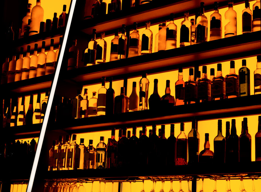 Rows of bottles sitting on shelf in a bar.
