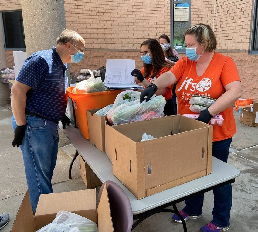 Food pantry volunteers work outside at the Jewish Federation of Kansas City amid the adoption of new pandemic-era health-and-safety protocols by Jewish institutions around the country.