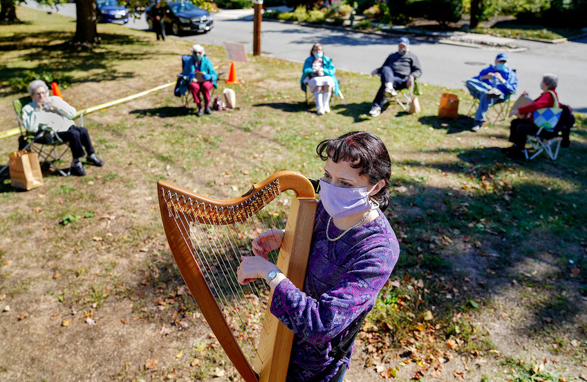 Harpist Laura Cole plays for a group from the Kosher Senior Cafe as they eat lunch in Lippitt Memorial Park.