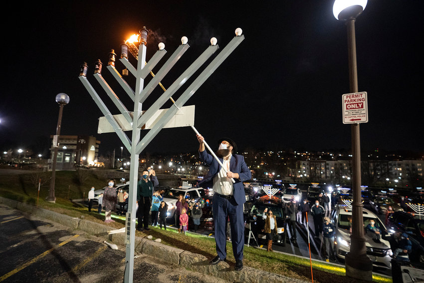 After a menorah car parade through Rhode Island on Dec. 13,  Rabbi Aryeh Laufer lights the menorah set up outside the Rhode Island State House.