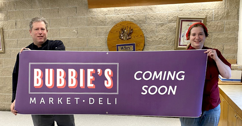 Jeffrey Ingber and Freda Ronkin hold the sign that will be displayed in the window of the new market and deli they plan to open soon.