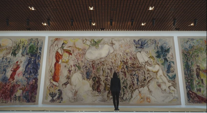 As part of Beit Avi Chai's online offerings, Israeli journalist Romy Neumark, center, narrates a series of short films on artistic works that bring Jewish holidays to light, including this painting by Marc Chagall at Israel's Knesset.