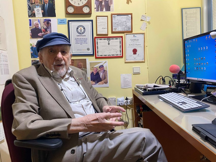 Longtime radio journalist Walter Bingham sits in his office behind a wall filled with memorabilia, including a telegram regarding an award he won from the United Kingdom's King George VI.