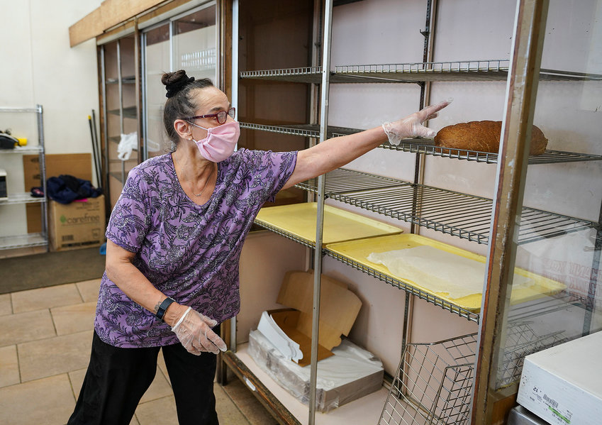 Rainbow Bakery employee Renee Lombardi reaches for one of the last loaves of bread.