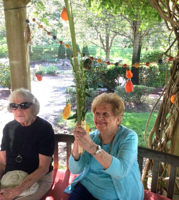 Residents enjoy the sukkah in the garden at the Phyllis Siperstein Tamarisk Assisted Living Residence in Warwick.