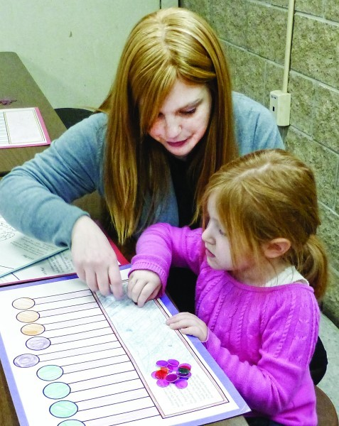 Leeba Laufer and her mother play at one of the booths at the pre-K Hanukkah program on Dec. 22.