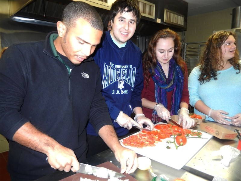 URI students (left to right) Michael Bonilla, Reuven Hoffman, Bridget Holte and Olivia Tagliaferri chop vegetables for the shakshuka before cooking begins.