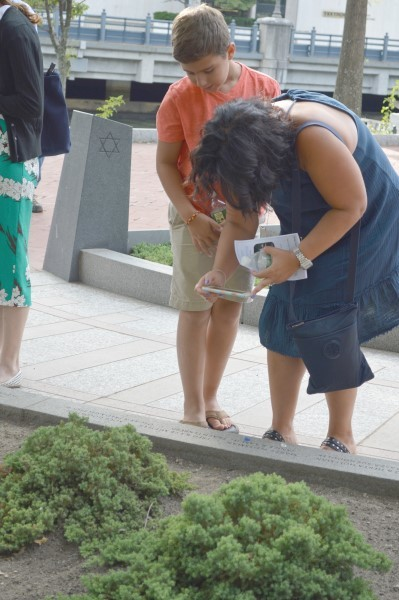 At the Aug. 28 ceremony, visitors had a chance to photograph survivor's names etched in stones along the pathway. Gov. Gina Raimondo, far right, spoke to the crowd.