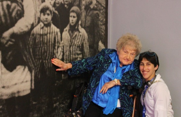 In Block 6 at Auschwitz with Eva in front of the liberation photo. Eva is pointing at her 10-year-old self, holding Miriam's hand.