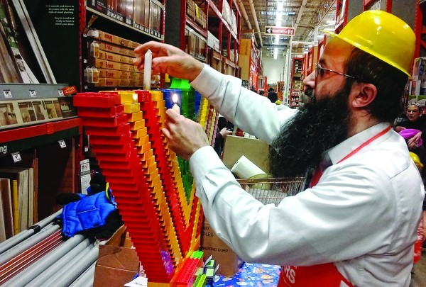 Rabbi Yossi Laufer lights a menorah made of Legos during a menorah-making workshop at Home Depot.