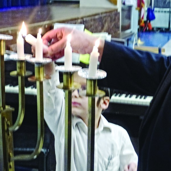 PHDS First-grader Yerucham Lapin lights the menorah at the Chanukah performance on Dec. 19.