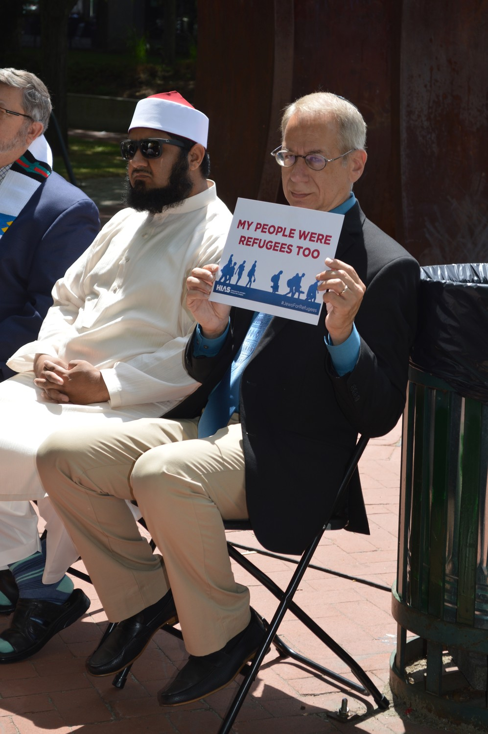 Rabbi Howard Voss-Altman holds a sign from HIAS