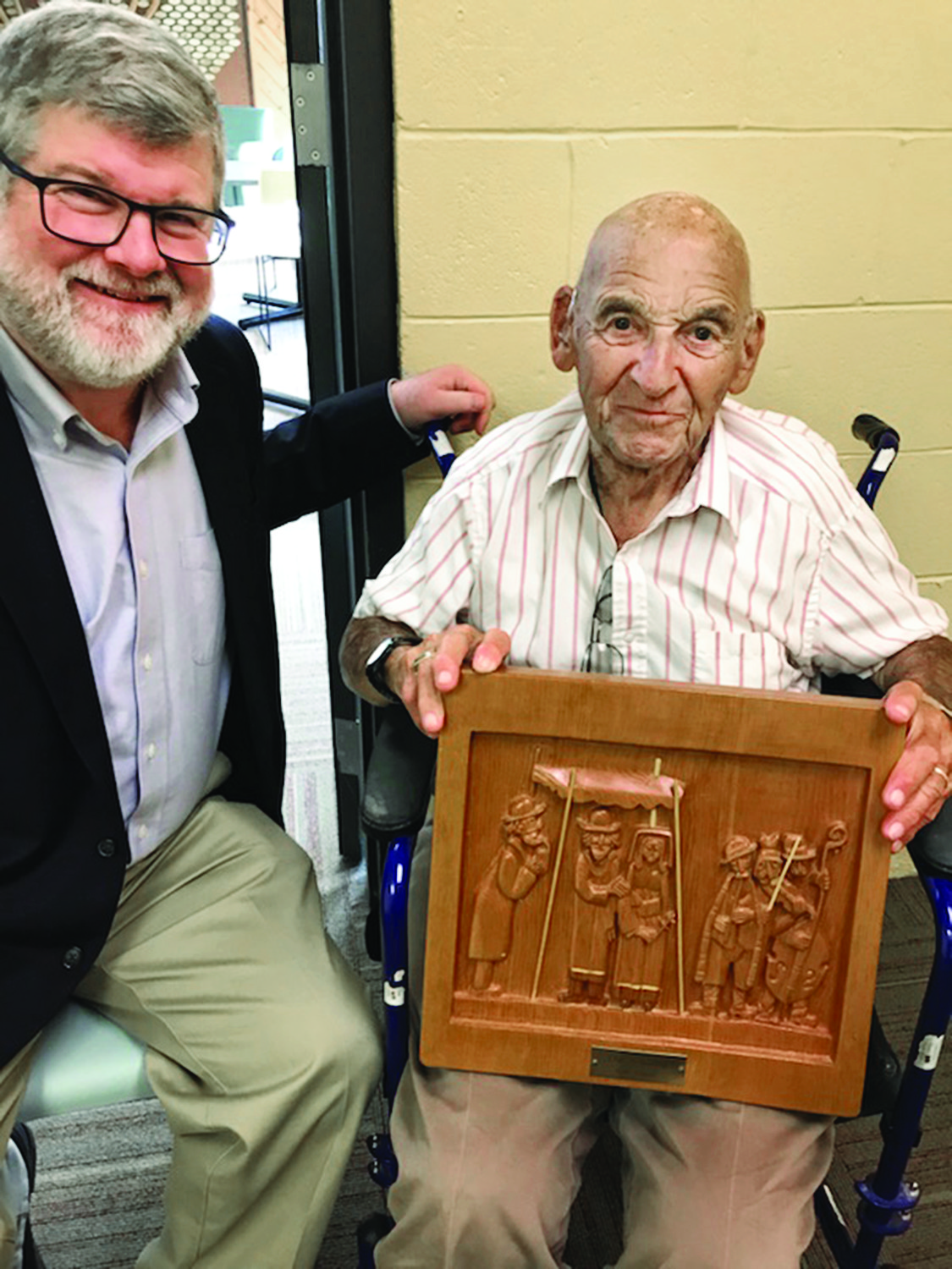 Rabbi Jeffrey Goldwasser with Sam Nelson who is holding his wood carving.