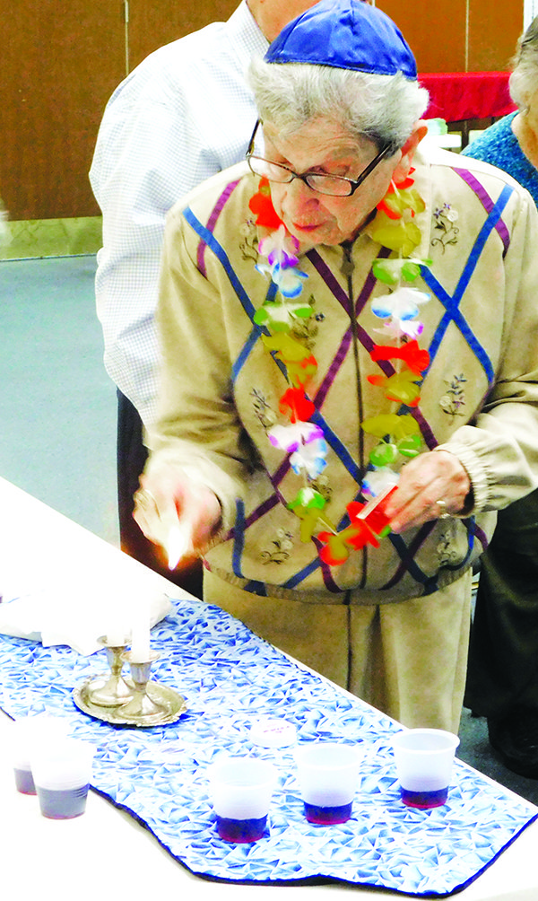 Tillie Orleck lights Shabbat candles.