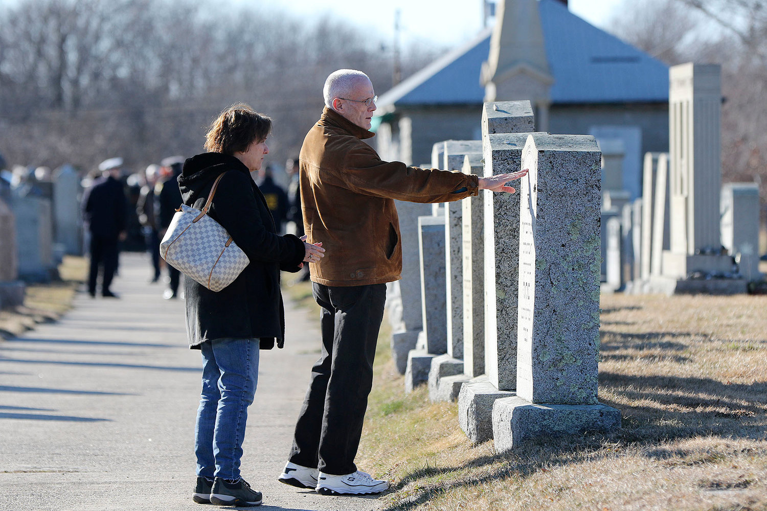 Cathy Horvitz, of Westwood, MA, left, and Ken Rapisa, of Fall River, right, look over the grave stones in the cemetery.   They did not know each other before this day.