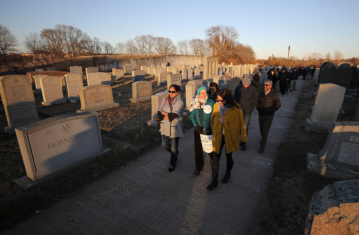 People walk through the cemetery after the ceremony.