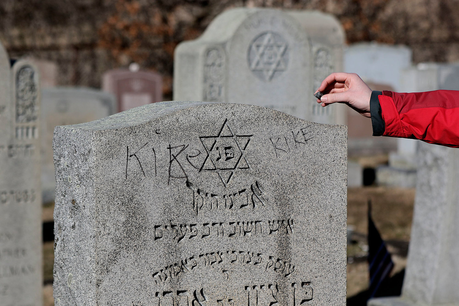 Ethan Gitlin, of Providence, places a stone on a grave marker.