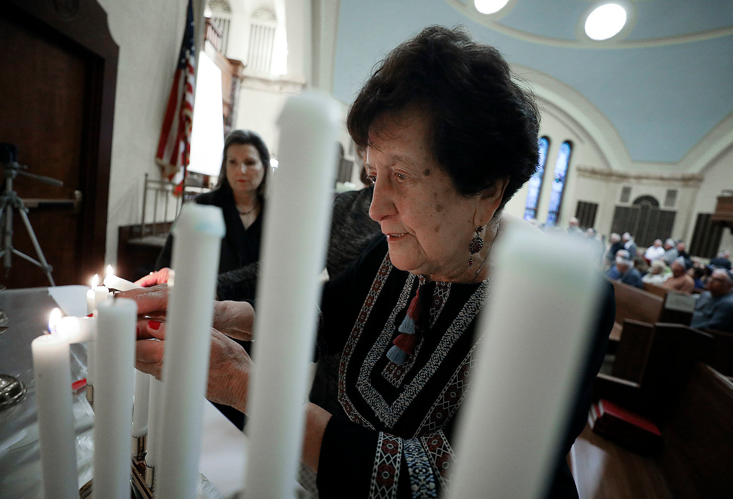 Alice Eichenbaum, of Providence, lights a candle at the beginning of the ceremony.   She was in a concentration camp in Bulgaria in WWII.  Jewish Rhode Island/Glenn Osmundson