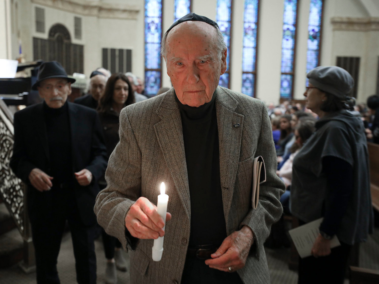 Albert Silverstein, of Pawtucket, lights a candle at the beginning of the ceremony. He was transported out of Austria as a youth.   Jewish Rhode Island/Glenn Osmundson