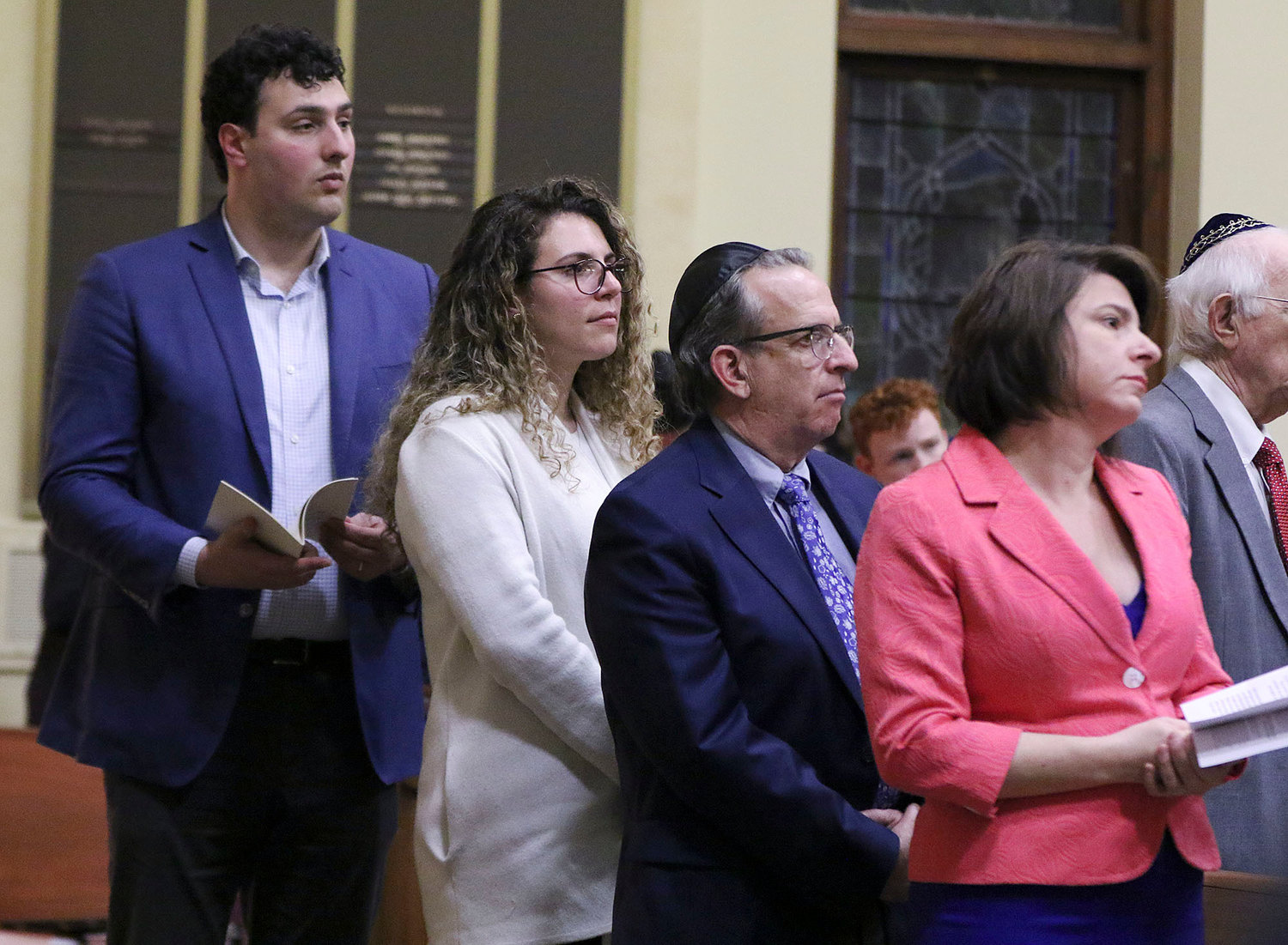 Four state legislators were honored  who sponsored a bill requiring the teaching of the holocaust and genocide studies in RI schools.  They are l to r: Former Rep. Aaron Regunberg, Rep. Katherine Kazarian, Sen. Josh Miller, and Sen. Gayle Goldin.  They are shown listening to local people listed their relatives that were killed in concentration camps.   Jewish Rhode Island/Glenn Osmundson