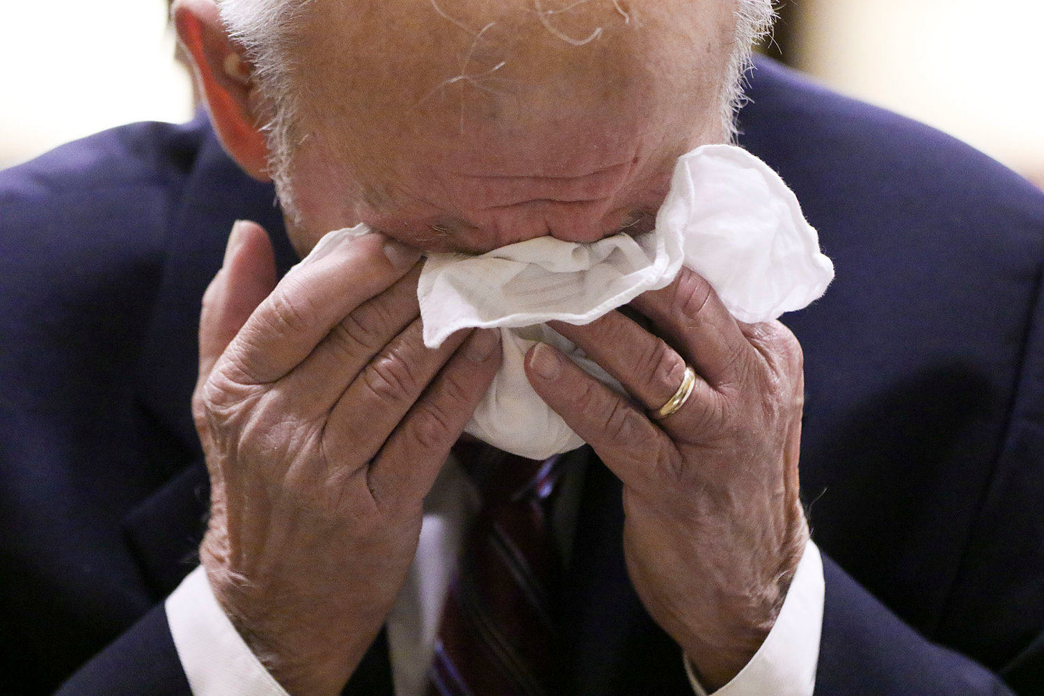 A man wipes his eyes while listening to people tell of family members killed in the holocaust. Jewish Rhode Island/Glenn Osmundson