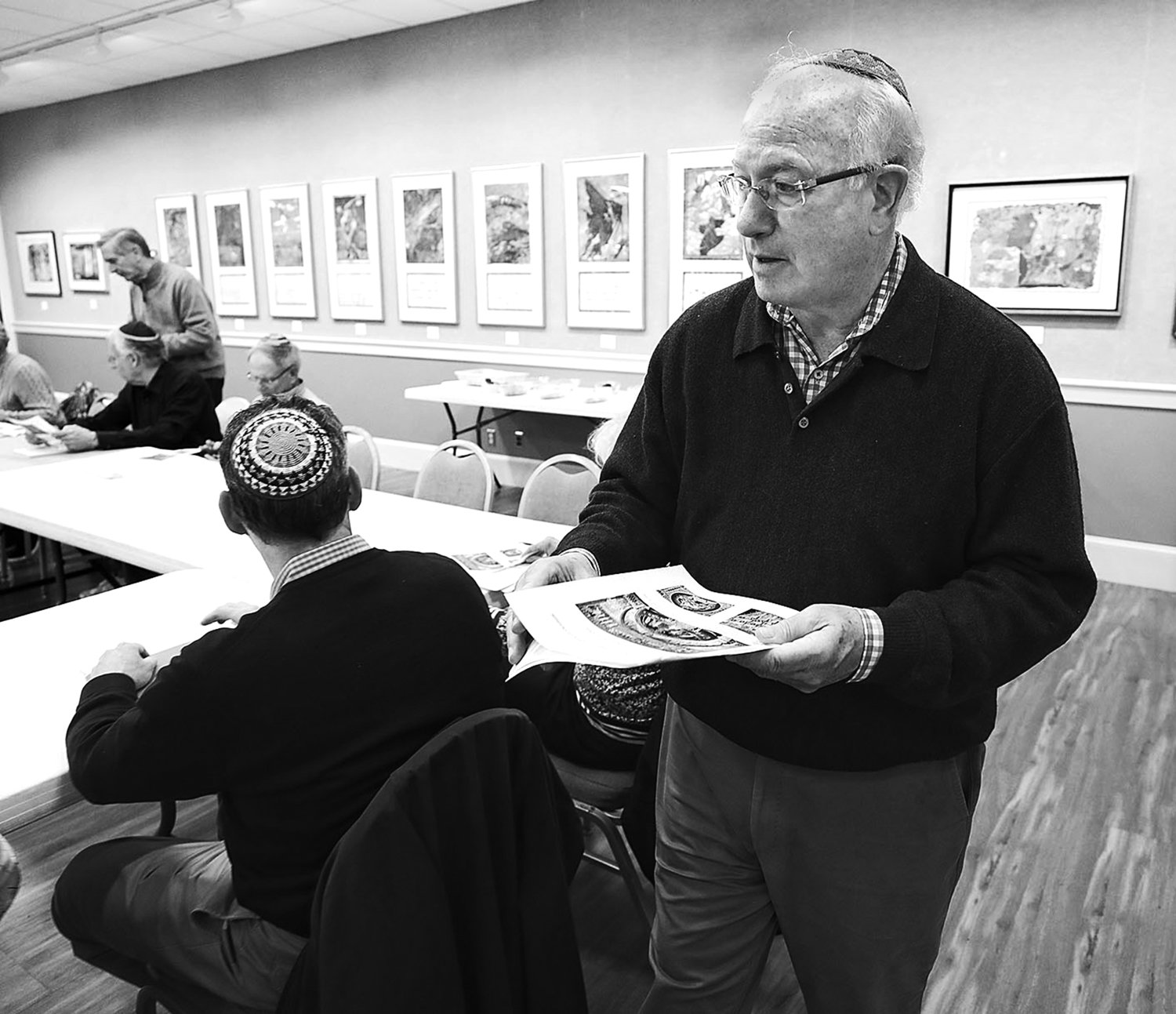 Rabbi Wayne Franklin passes out materials at the beginning of an adult education class.