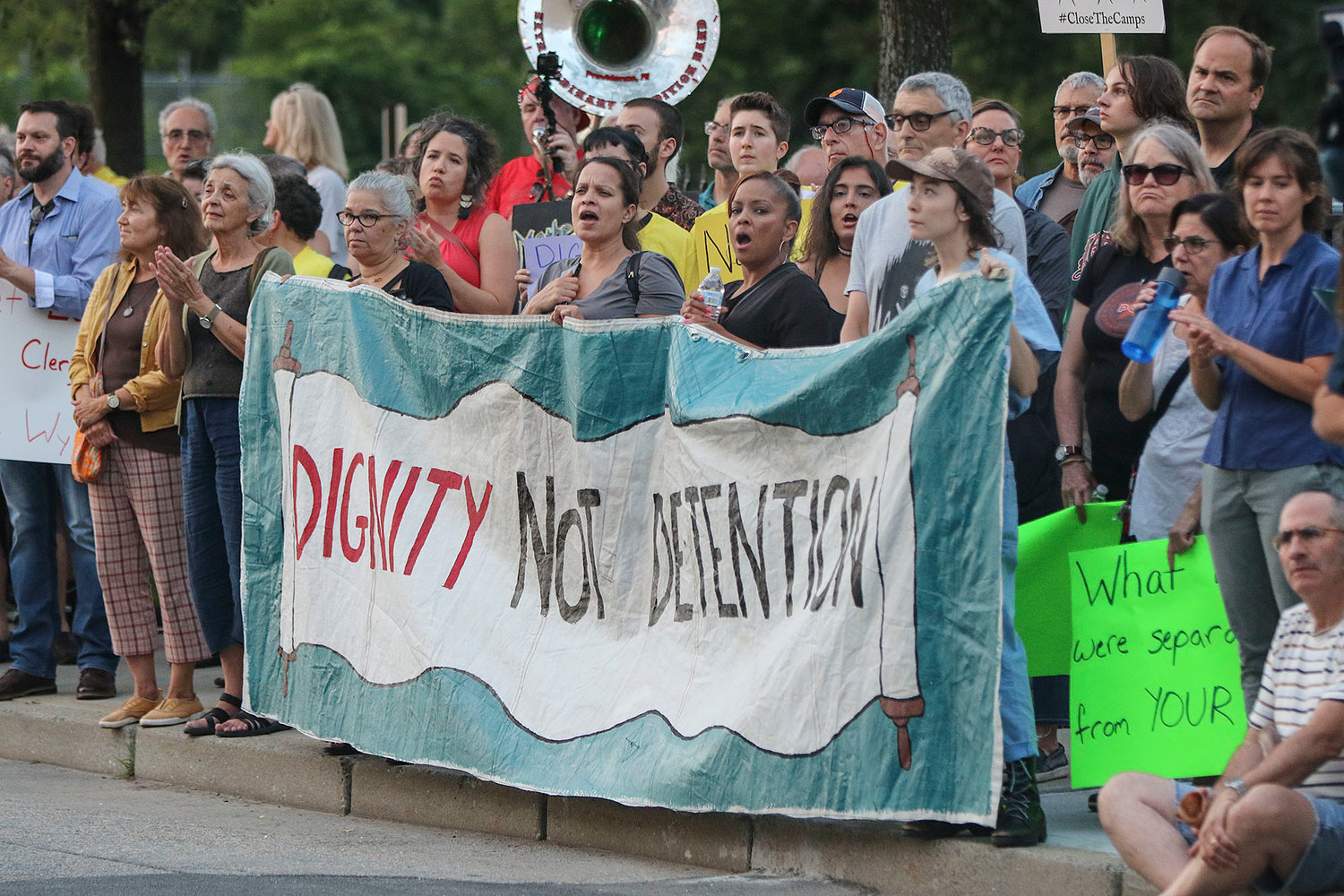"CENTRAL FALLS, RI--Wednesday August 14, 2019--Never Again in Now march/rally from Jenks Park to the Wyatt detention facility ""to continue demonstrating against the prison's contract with ICE, highlight ICE's inhumane treatment of immigrants here in RI and across the country, and work to shut down ICE's deportation machine for as long as possible.""  PICTURED IS:  Protesters on the sidewalk across the street from the detention center.   Jewish Rhode Island/Glenn Osmundson"