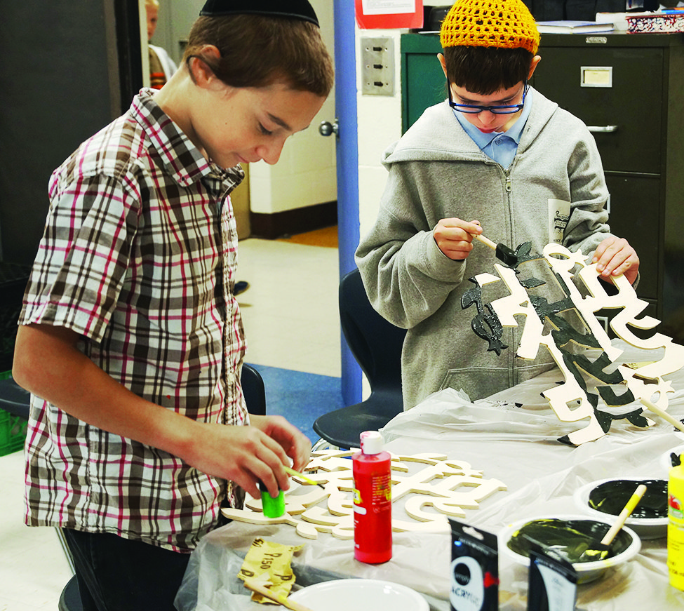 PHDS seventh-grade students, Shlomo Lapin and Simcha Abrahim paint decorations for their Sukkah.