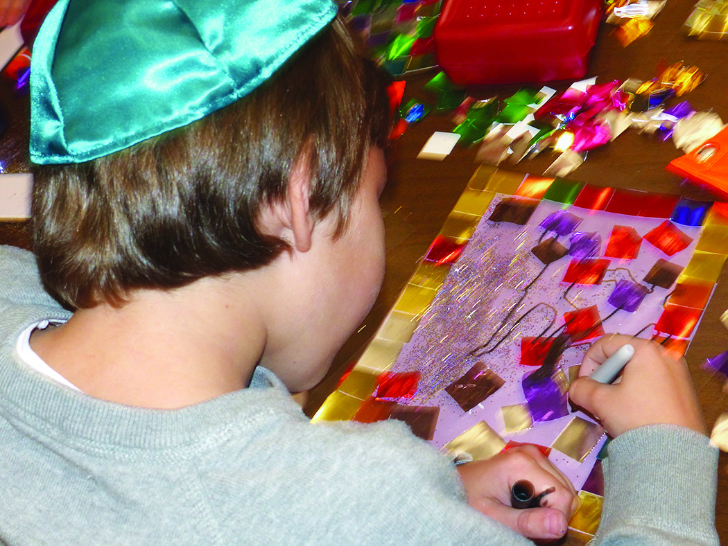 PHDS third-grade student, Justin Brosious adds detail to his Sukkah decoration.