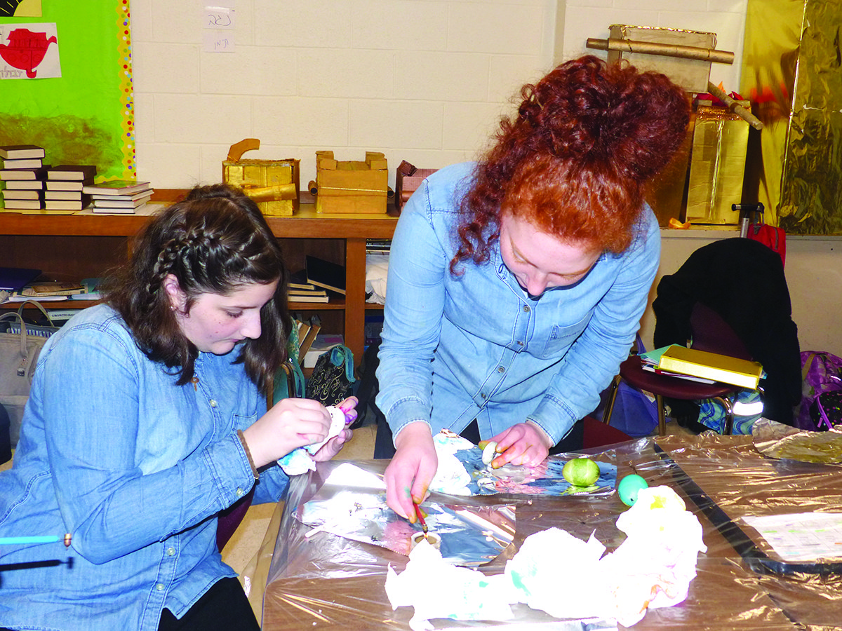 PHDS eighth-grade students, Gitty Barker and Atara Bielory work on their Sukkah decorations.