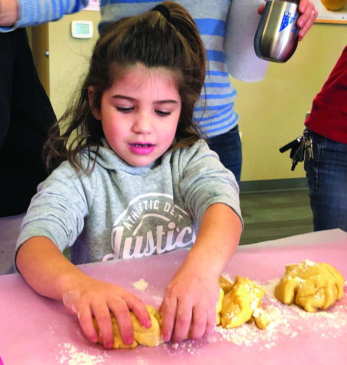 Ayla Kushner works on shaping her challah.