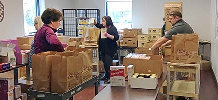 Helping to packing bags for food pantry clients are Erin Minior, JCS president and CEO, Jeremy Thayer, JCS clinical supervisor, and Ellen Kaye, JCS volunteer.