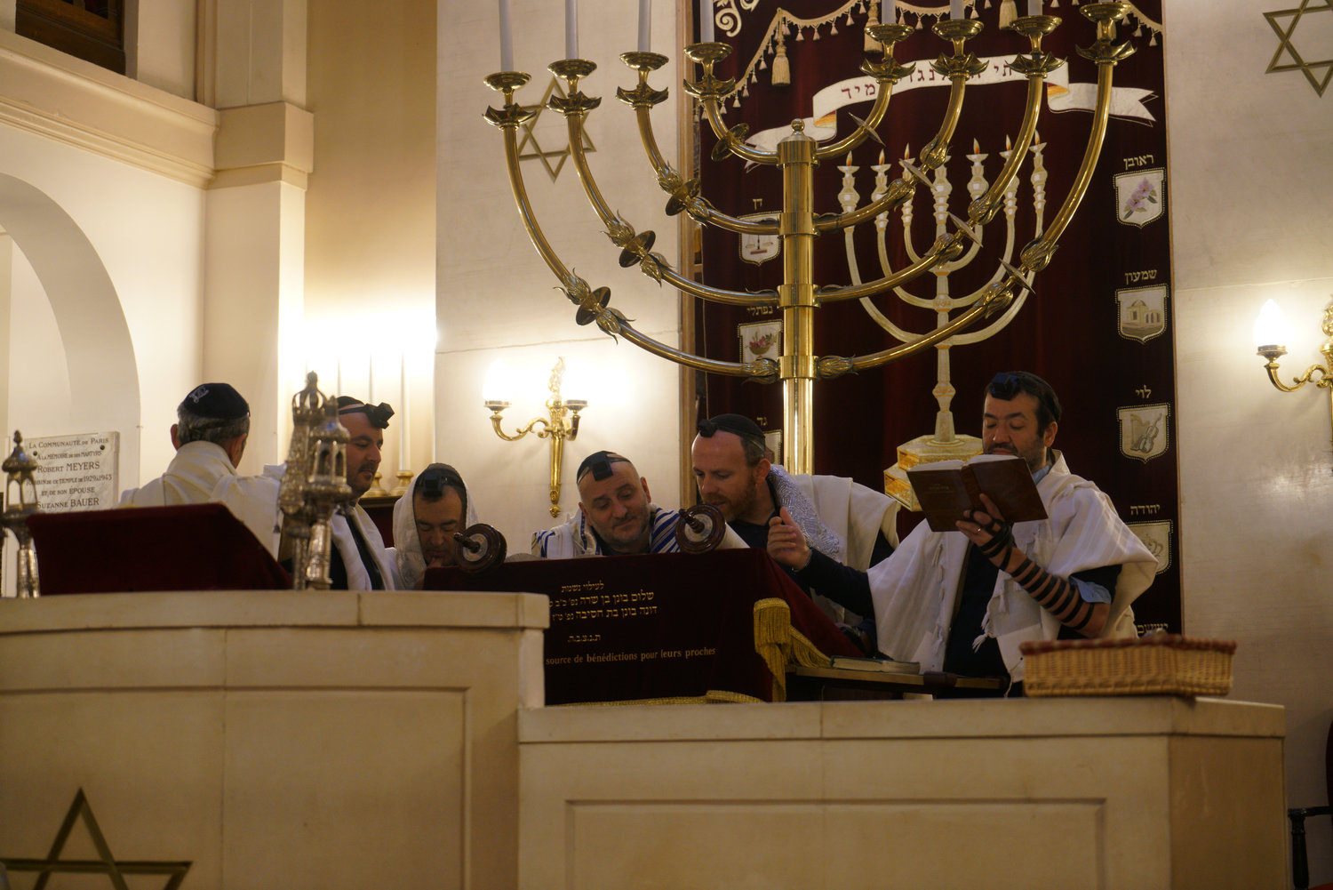 Rabbi Michael Azoulay, second from right, reading the Torah with congregants at the synagogue of Neuilly-sur-Seine, a Paris suburb, Dec. 11, 2017.
