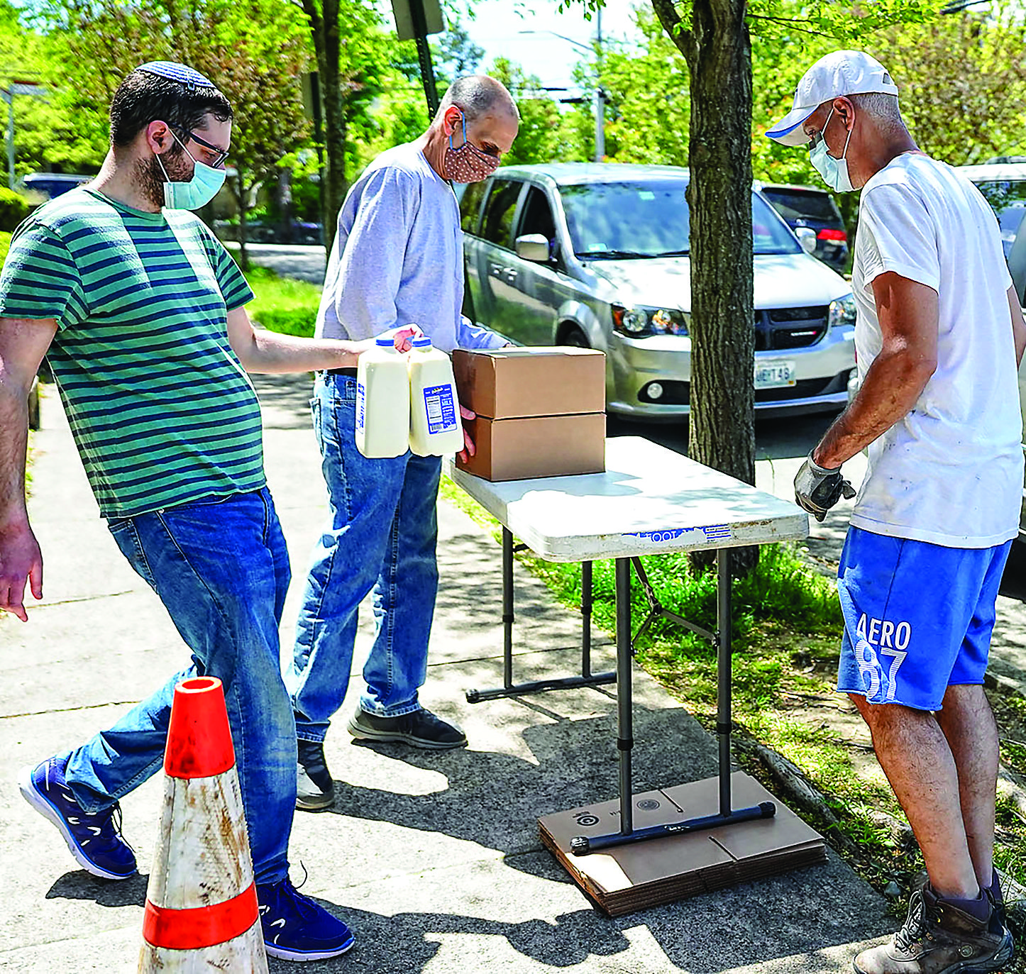 On a recent Friday, cars line up outside of Congregation Beth Sholom in Providence for a free Kosher food program program aimed at feeding children under age 18 while volunteers bring out milk and boxed meals..