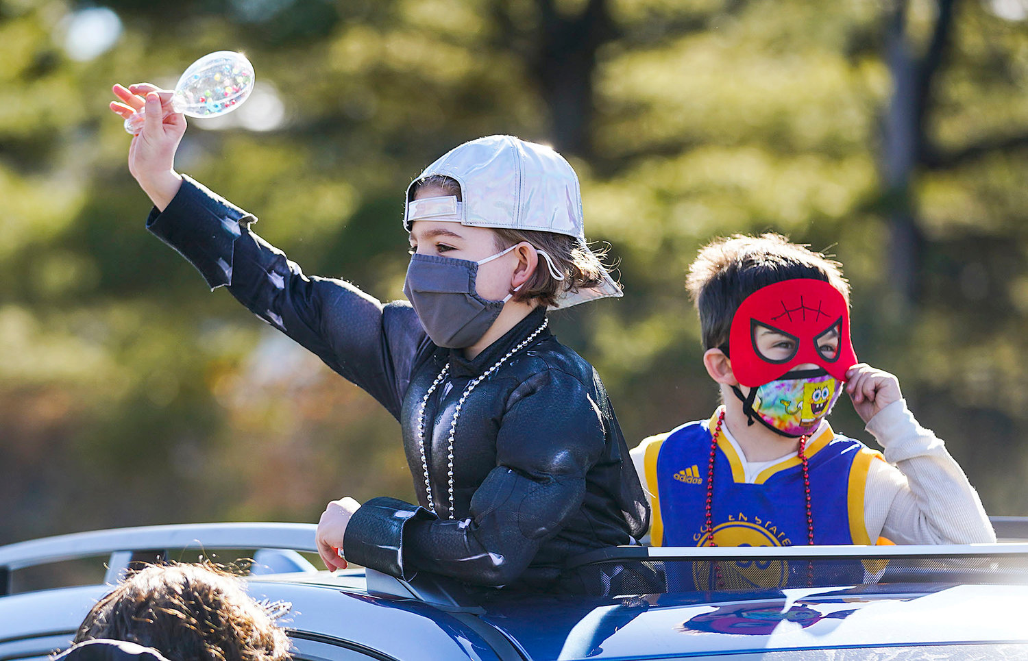 Micah Bogad, 9, left, and Noah Holt, 6, right, both of Providence, poke through the sun roof with a mask and a maraca they received at the event.