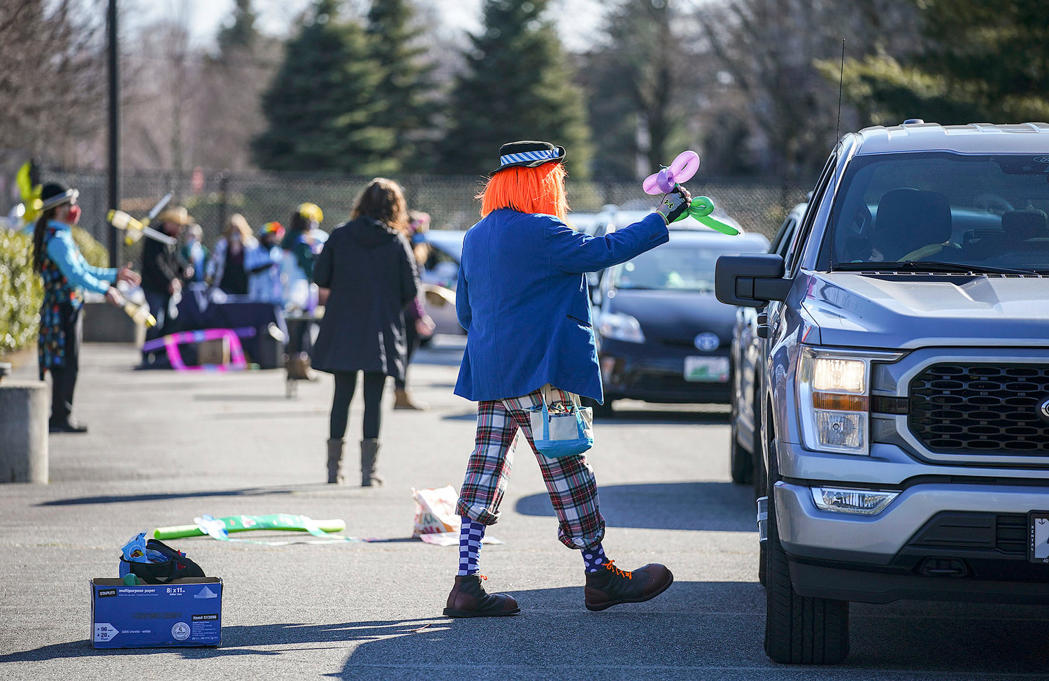 """Disco"" (a.k.a. Sam Miller), of Providence passes a balloon animal to the occupants of one of the cars"