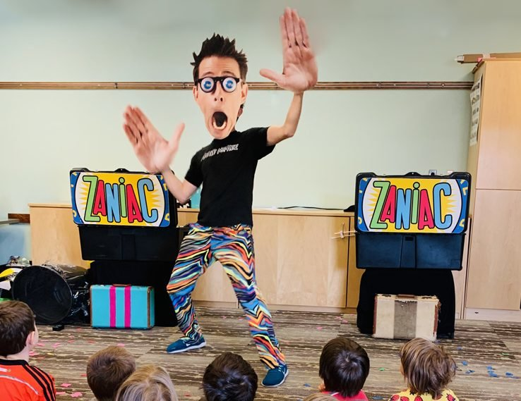 Alex Zerbe transforms into a life-sized dancing bobblehead, triggering laughter and squeals from his young audience.
