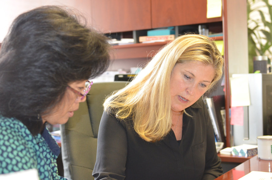 Administrative assistant Kyong Bertsch at work with Tracy Stirrett, right.