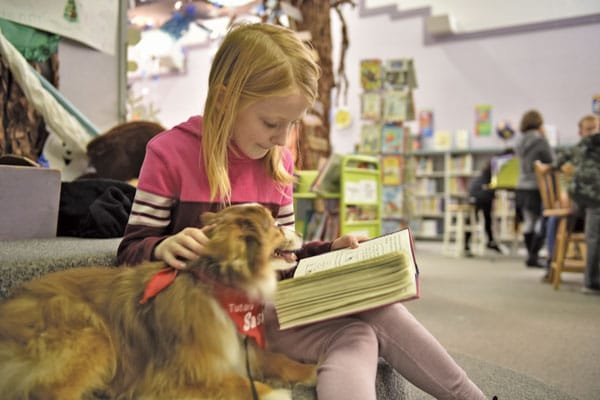 Third-grade student Scarlett Struthers enjoys reading aloud with Sasha.