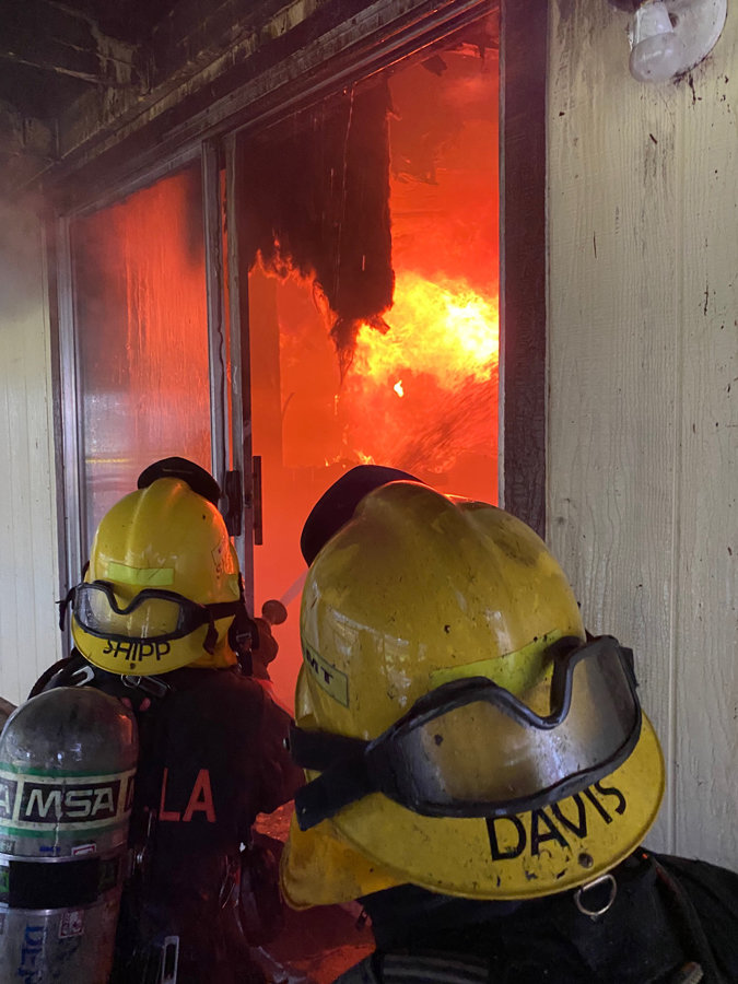 Firefighters Ami Shipp and Tim Davis douse flames late in the exercise.