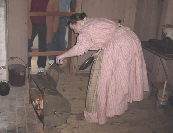 Thanksgiving 19th century-style: Checking the turkey at Old Bethpage Village Restoration, in a demonstration of some of the foods prepared for an old-fashioned holiday 