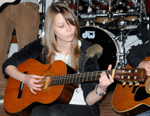 Kristen Schwenk, a student at The Harriet Eisman Community School, played acoustic guitar at the talent show on April 29.
