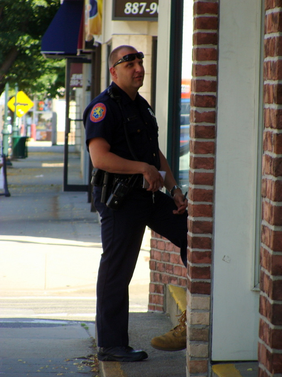 A 4th Precinct officer questions proprietors across the street from the Bank of America.