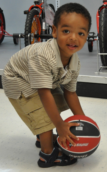 Nykeil Naggie, 23 months, finds a basketball he wants to take home.