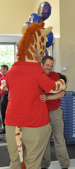 Geoffrey the Giraffe gives store manager Ken Farrell a big hug.