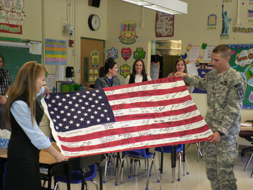 Pvt. Brian McGee, with his former principal Dr. Ellen Tiegerman, recently demonstrated to students how to properly fold an American flag at the School for Language and Communications Development in Glen Cove. The flag was autographed by members of his company, currently stationed in Iraq.