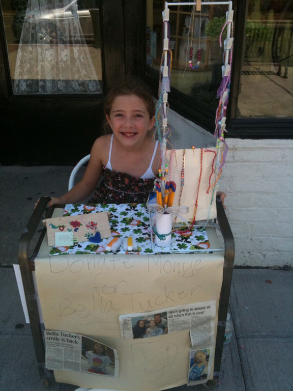 Keira Derrig, 9, whose mother owns the Lynbrook Irish Shop, sells bracelets to raise money for Bella Tucker, who underwent quadruple amputation surgery in April. Keira read about Bella in the Herald. The two girls have never met.
