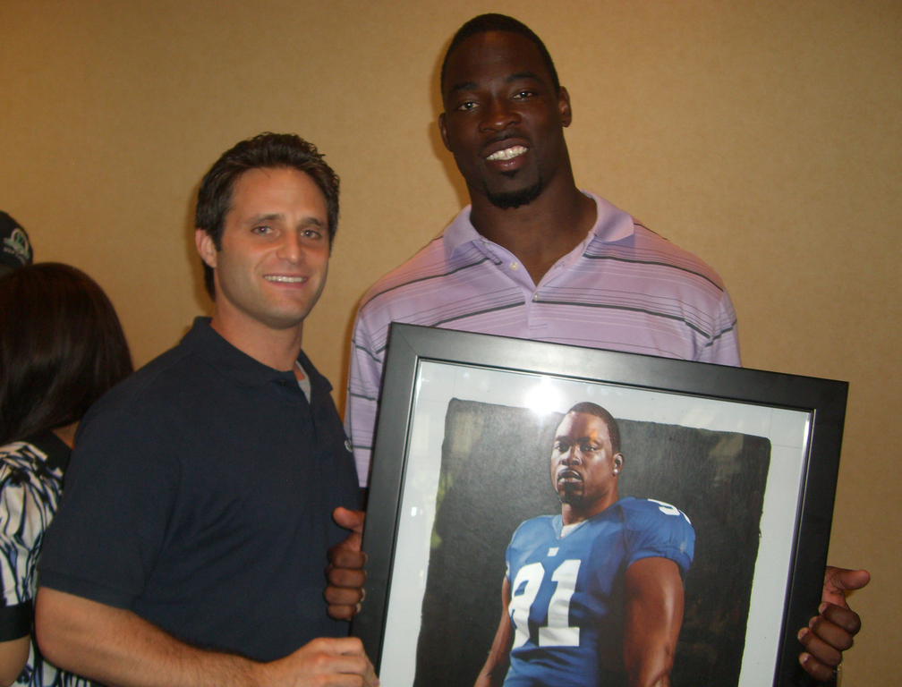 Cedarhurst artist Adam Port, left, with the New York Giants' Justin Tuck and Tuck's image illustrated by Port, who is selling more than 40 pieces of original artwork to raise money for Ronald McDonald House.