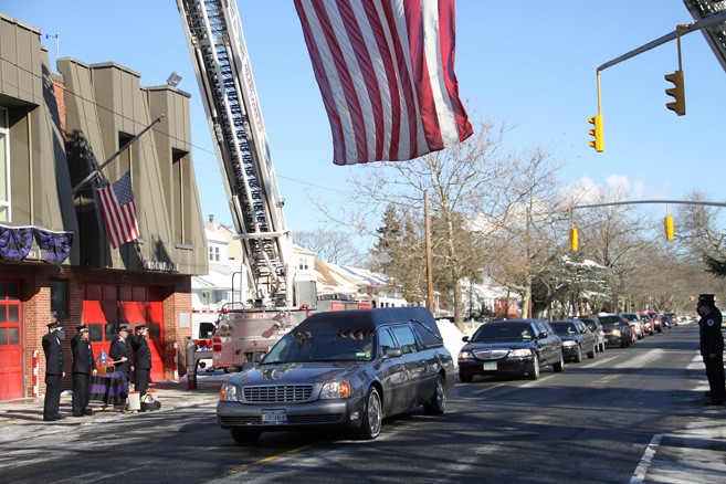 Firefighters saluted as M. George Caracost's funeral procession passed in front of the Island Park Fire Department fire house. Caracost was an IPFD 
